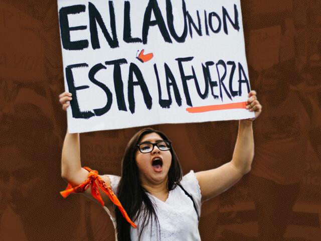 Woman rising a sign that reads En la unión está la fuerza (Strentgh is within unity)